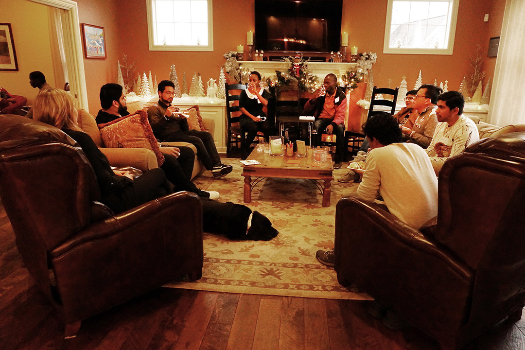 'People gather in living room decorated for the holidays.'